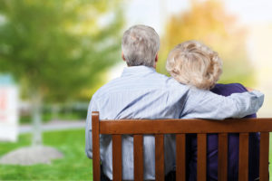 elderly man and woman on a park bench