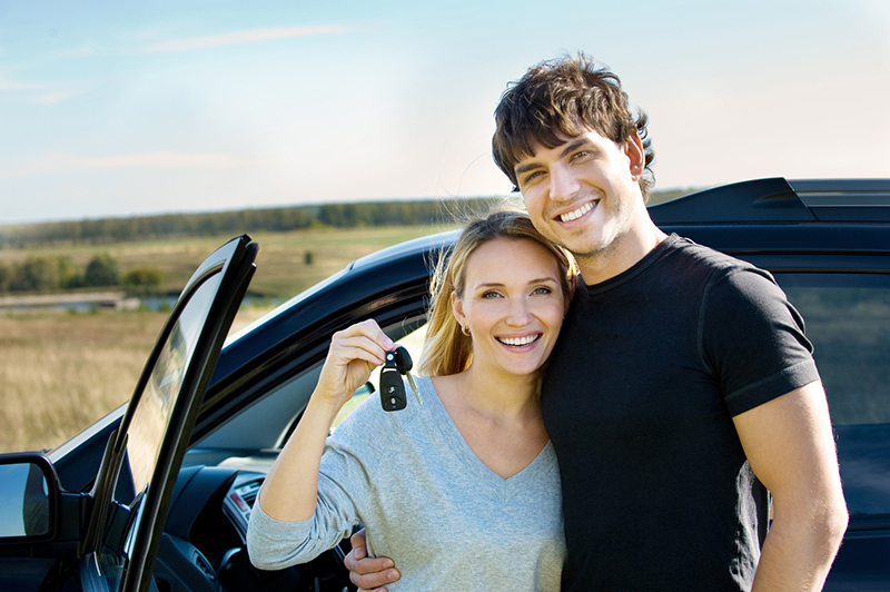 a couple standing in front of a car smiling
