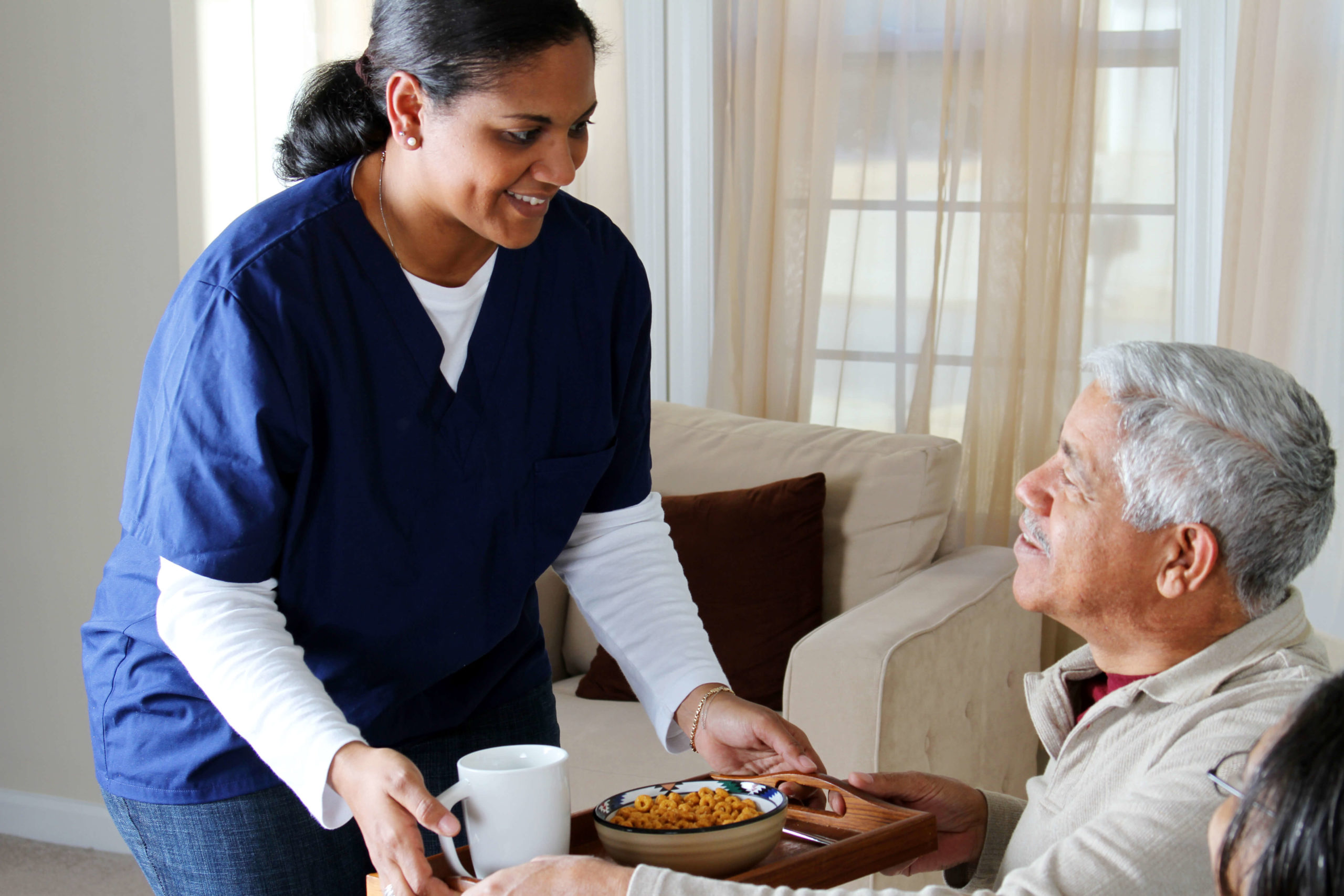 a nurse giving an elderly person a meal
